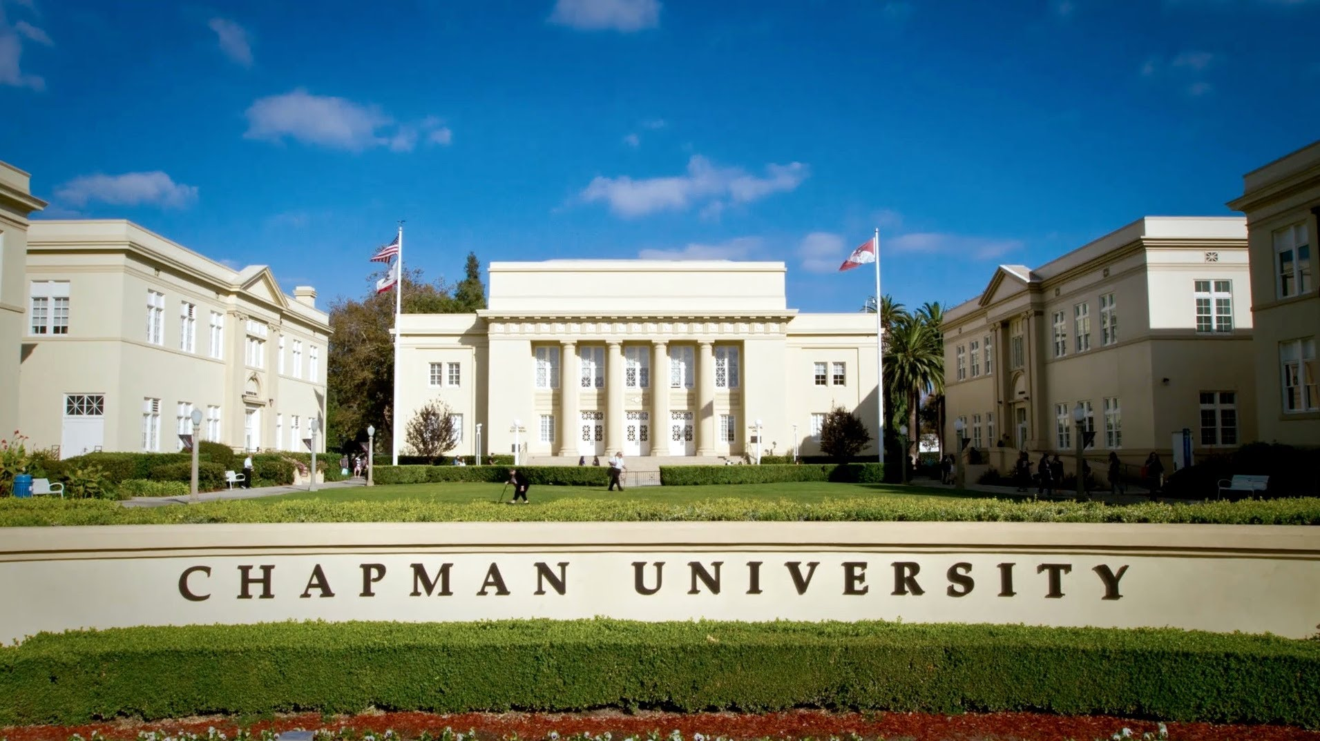 Exterior shot of Memorial hall with the Chapman University sign in the foreground.