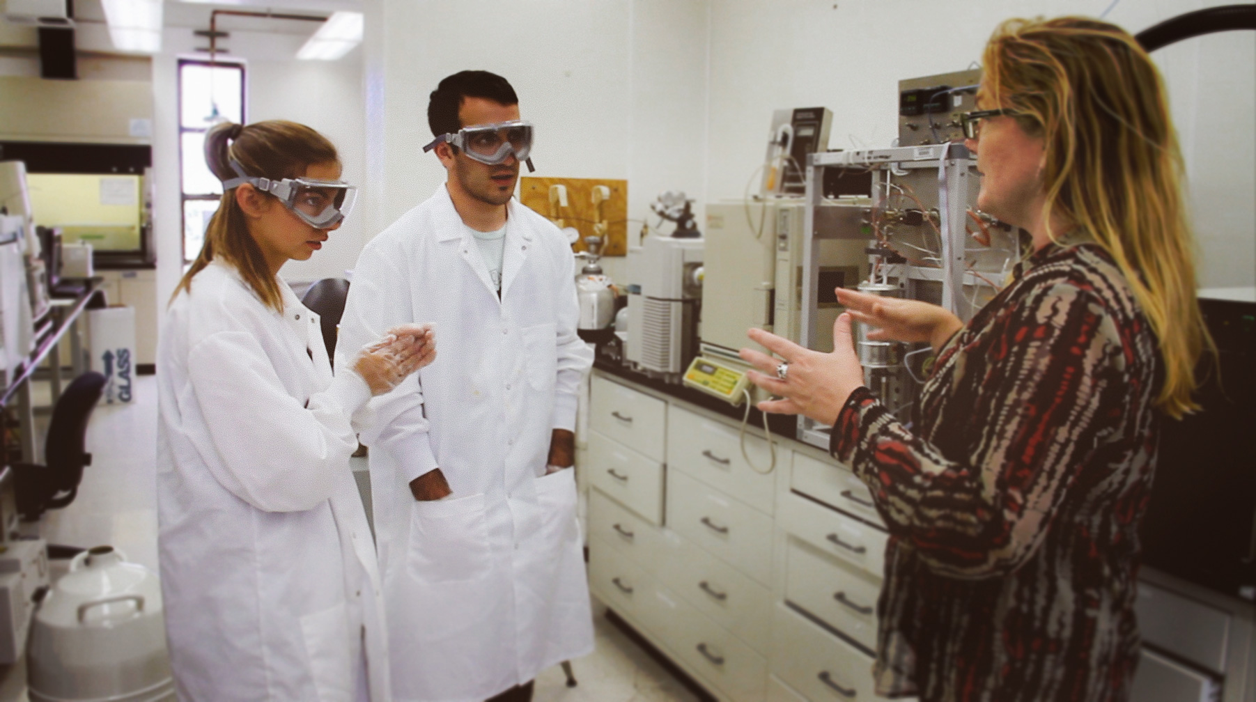 Two students in lab coats talking to a nicely-dressed woman
