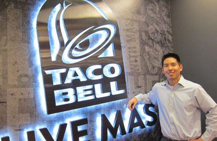 Man standing in front of Taco Bell logo.