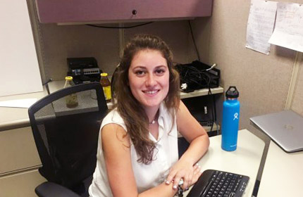 Chapman student sits at desk for internship.
