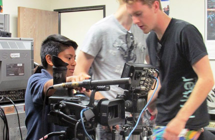 Young student on camera being helped by college student.