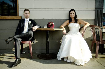 Two chapman alumni in wedding attire sitting in chairs