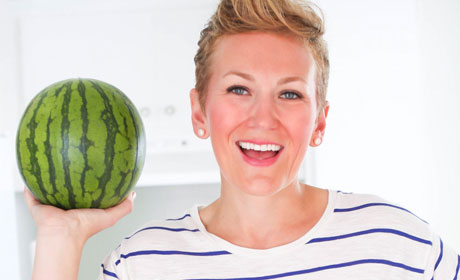 Woman holding watermelon and smiling.