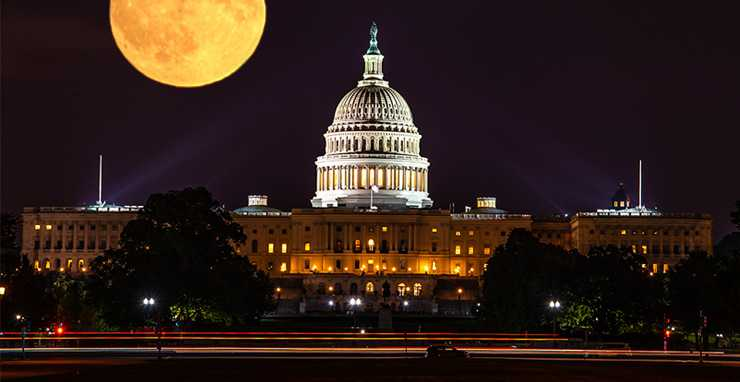 US Capitol building with the moon behind it
