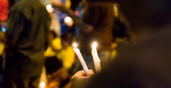 Close up of lit candle at Chapman candle vigil at night