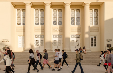 Student walking in front of Memorial Hall at Chapman University