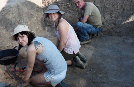 three people digging in a hole