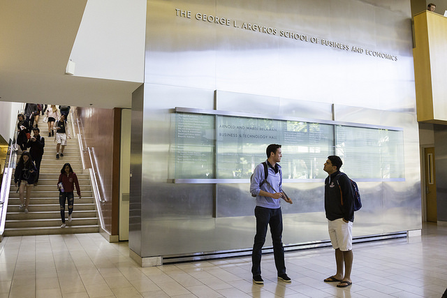 Image of students walking around in the background of the lobby of Beckman Hall, the business school building at Chapman University
