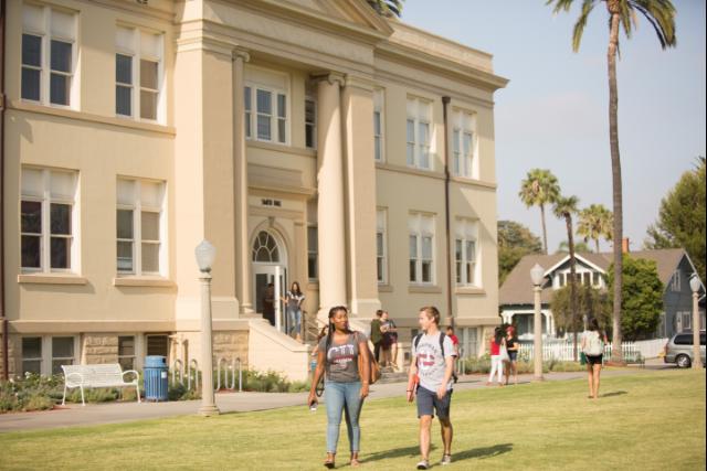 two students walking across Memorial Lawn talking