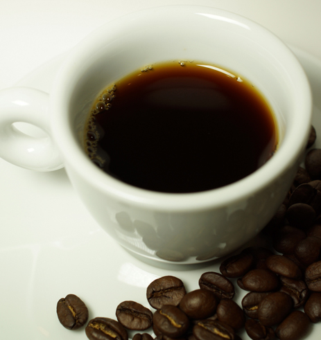 Image of a full cup of coffee and some coffee beans in lower right corner.
