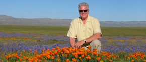 Huell Howser in a field of flowers
