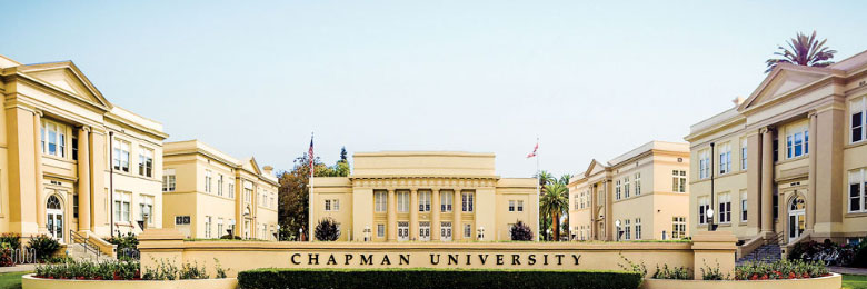 group of historic buildings with a sign in front that reads chapman university